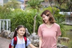 Moeder en kindholdingshanden die naar school gaan stock afbeelding