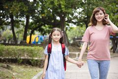 Moeder en kindholdingshanden die naar school gaan stock fotografie