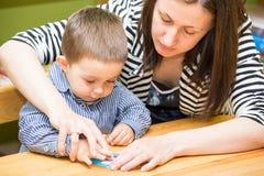 Moeder en kindjongenstekening samen met kleurenpotloden in kleuterschool bij lijst in kleuterschool Stock Afbeeldingen