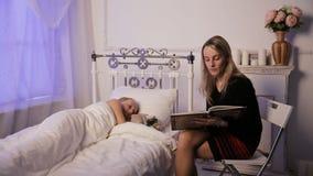 Moeder en kindlezingsboek in donkere slaapkamer stock video