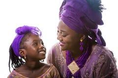 Moeder en kindmeisje die aan elkaar kijken Afrikaanse traditionele kleding stock fotografie