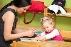 Moeder en kindmeisjestekening samen met kleurenpotloden in kleuterschool bij lijst in kleuterschool Stock Fotografie