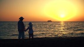 Moeder en kindsilhouetten en zonsondergang over het overzees stock video