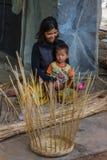 Moeder en kindzitting in hun Cambodjaans dorp Stock Foto