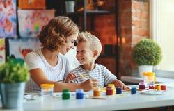 Moeder en kindzoon het schilderen trekt in creativiteit in kleuterschool stock fotografie