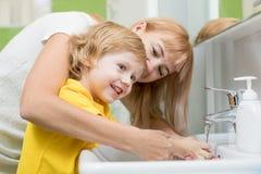 Moeder en kindzoon hun wassen dient de badkamers in Zorg en zorg voor jonge geitjes stock fotografie