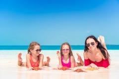 Moeder en kleine dochters die van tijd genieten bij tropisch strand stock afbeelding
