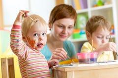 Moeder en kleine jongens die messily met verven spelen Stock Afbeelding