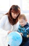 Moeder en leuk jong geitje die bol samen bestuderen Royalty-vrije Stock Foto's