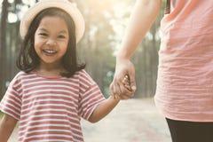 Moeder en leuk kindmeisje dat holdingshand glimlacht stock foto's