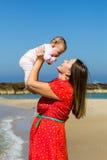 Moeder en leuk weinig babymeisje op het strand Royalty-vrije Stock Foto's