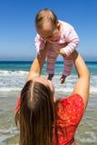 Moeder en leuk weinig babymeisje op het strand Royalty-vrije Stock Afbeeldingen