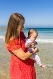 Moeder en leuk weinig babymeisje op het strand Stock Foto