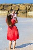 Moeder en leuk weinig babymeisje op het strand Stock Afbeelding