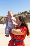 Moeder en leuk weinig babymeisje op het strand Stock Afbeeldingen
