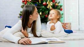 Moeder en leuk weinig dochter die op de vloer liggen en boek lezen bij Kerstmisvooravond Stock Foto