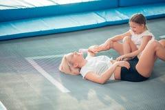 Moeder en meisje het spelen bij speelplaats en het liggen op een trampoline royalty-vrije stock afbeelding