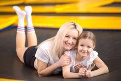 Moeder en meisje het spelen bij speelplaats en het liggen op een trampoline royalty-vrije stock foto's