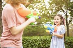 Moeder en meisjes die waterkanonnen in het park spelen royalty-vrije stock afbeeldingen