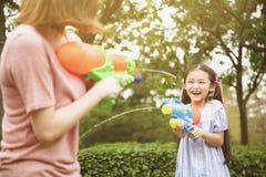 Moeder en meisjes die waterkanonnen in het park spelen royalty-vrije stock foto