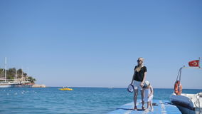 Moeder en meisjesgangen op pijler, schommeling door golven stock videobeelden