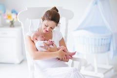 Moeder en pasgeboren baby in wit kinderdagverblijf Stock Foto's