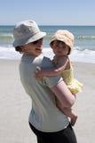 Moeder en peuter bij het strand Stock Foto's