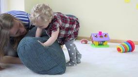 Moeder en peuter het kind speelt met blauw groot hoofdkussen en toont ware emoties stock footage