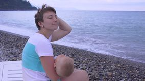 Moeder en slaapbaby op het strand stock video