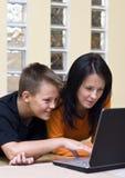 Moeder en tiener met laptop Stock Afbeeldingen