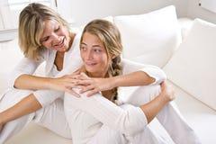 Moeder en tienerdochter die thuis ontspannen royalty-vrije stock afbeelding