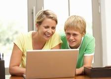 Moeder en TienerZoon die Laptop thuis met behulp van Stock Foto's
