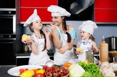 Moeder en twee dochters in de keuken stock afbeelding