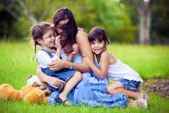 Moeder en twee dochters die in gras spelen royalty-vrije stock afbeeldingen