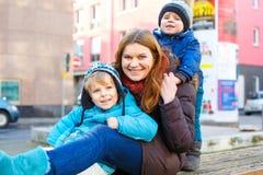 Moeder en twee jong geitjejongens die op straat in de winter koesteren Stock Afbeeldingen