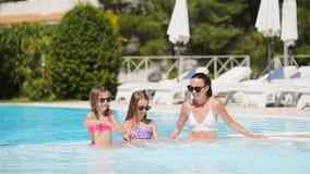 Moeder en twee jonge geitjes die de zomer van vakantie in luxe zwembad genieten stock footage