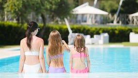 Moeder en twee jonge geitjes die de zomer van vakantie in luxe zwembad genieten stock videobeelden