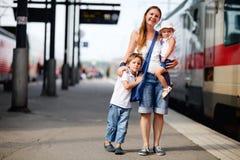 Moeder en twee jonge geitjes die op trein wachten Stock Foto