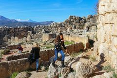 Moeder en twee kinderen bij ruïnes van oude Mycenae Griekenland met snowcapped mountians op achtergrond 1 5 2018 royalty-vrije stock foto's