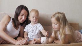 Moeder en twee kinderen die geld besparen aan spaarvarken Familie het verdienen geld voor toekomst Het Concept van de investering stock footage