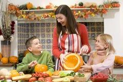 Moeder en twee kinderen die pompoenen snijden Royalty-vrije Stock Afbeeldingen