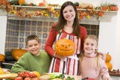Moeder en twee kinderen die pompoenen snijden Stock Afbeeldingen