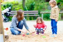 Moeder en twee kleine kinderen die op speelplaats spelen royalty-vrije stock afbeelding