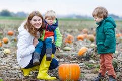 Moeder en twee kleine zonen die pret op pompoenflard hebben. Royalty-vrije Stock Foto