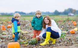 Moeder en twee kleine zonen die pret op pompoenflard hebben Stock Fotografie