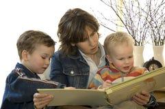 Moeder en twee lezing van de zoon een boek stock foto