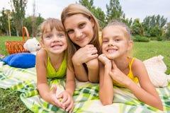 Moeder en twee meisjes die op gras op een picknick en een pret de liggen onderzoeken het kader Royalty-vrije Stock Afbeeldingen