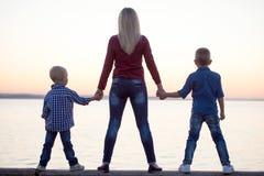 Moeder en twee zonen de gang op de promenade en let op de zonsondergang Royalty-vrije Stock Foto