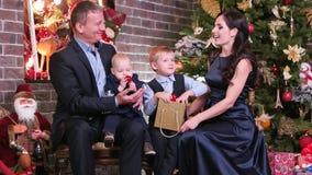 Moeder en vader die aan een vers luisteren dat oudste zoon, Gelukkige familie het vieren Nieuwjaar` s Vooravond, leuke babyzittin stock video