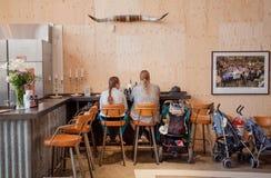 Moeder en vader die binnenfast-food restaurant met kinderwagens eten Royalty-vrije Stock Foto
